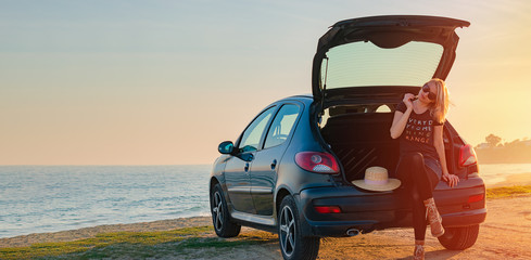 Young woman sits in a car trunk by the sea on the beach. Summer, sunset, road traveling concept. Copy space.