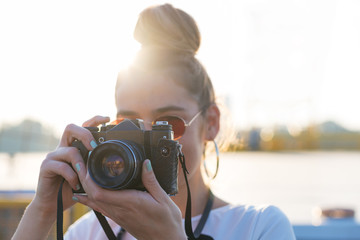 young woman photographer using a camera in bright daylight