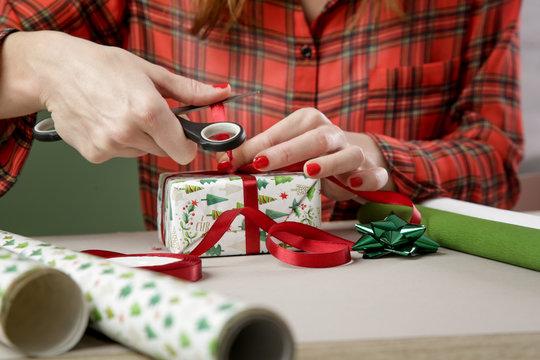Woman wrapping Christmas presents, winter hoildays, gifting season concept