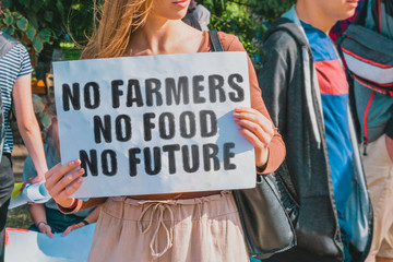 "The phrase "" No farmers. No food. No future "" drawn on a paper in woman hands. Caucasian woman with light hair holds a cardboard with an inscription. Business. Pressure on farmers"