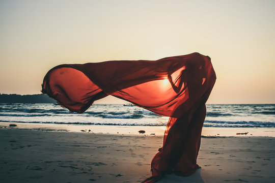 Creature in a red floaty robe standing on the beach sunset golden hour silhouette Ngapali beach Myanmar