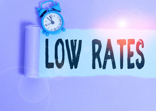 Text sign showing Low Rates. Business photo showcasing A cost of an item or service which is usualy at its smallest price Alarm clock and torn cardboard placed above plain pastel table backdrop
