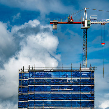A working Construction Sky Crane on a new high rise multistory building site with blue sky background. Australia.