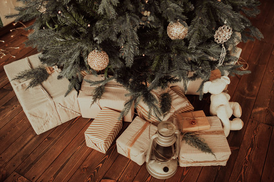 eco-friendly gift boxes in reusable fabric packaging and twine ribbon,in large numbers under the Christmas tree on a dark wooden parquet