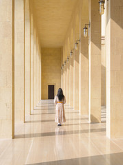 The back of woman with long hair long dress walking on perspective walkway to the door on building with sunlight shine thru background.