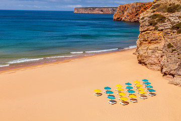 Deserted beach with colorful parasols in the Algarve Portugal