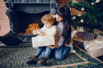 Beautiful mother in a white sweater. Family in a christmas decorations. Little boy in a room