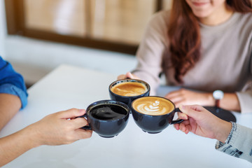 Closeup image of people enjoyed drinking and clinking coffee cups together on the table in cafe