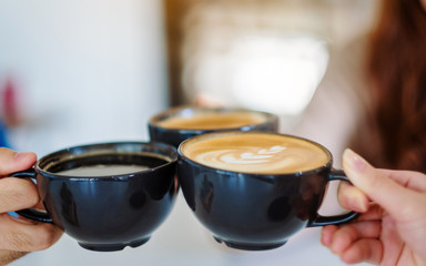 Closeup image of three people enjoyed drinking and clinking coffee cups in cafe