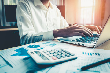 Businessman accountant or financial expert analyze business report graph and finance chart at...