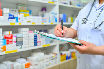 Doctor writing prescription with many medicine on shelves background