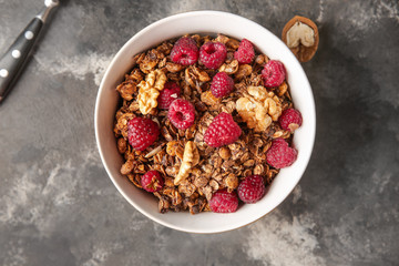 Bowl with tasty granola and berries on grunge background