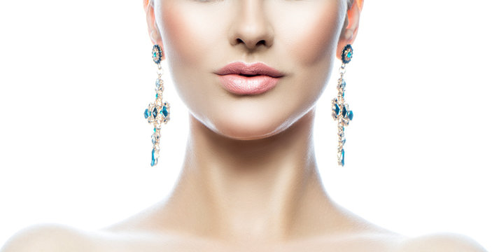 Lips, face, shoulders of beauty model woman with perfect skin, natural lipstick, jewelry big earrings. White background