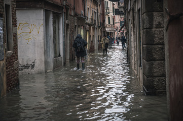 Poster Venetie Venice, Veneto, Italy; 11/15/2019: Locals and tourists endure the worst flood in more than 50 years in Venice lagoon. People pass the flooded streets of the city.
