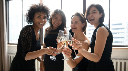 Happy beautiful women hold glasses look at camera celebrate party