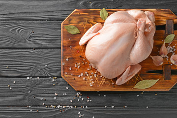 Foto op Aluminium Kip Raw chicken with spices on wooden background
