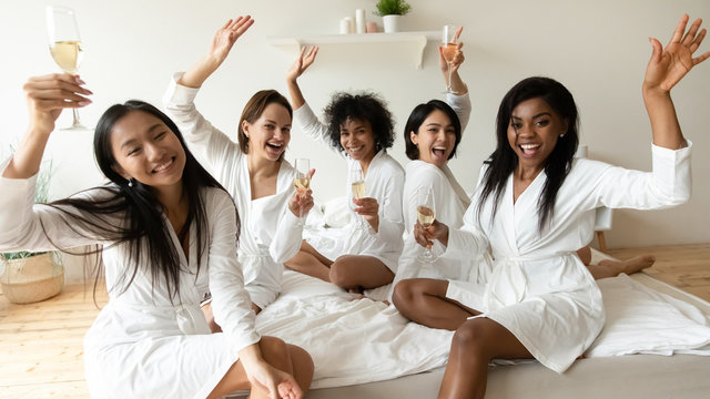 Happy diverse young women raise champagne glasses look at camera