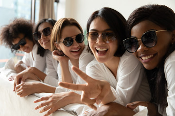Happy young adult attractive ladies wear sunglasses looking at camera