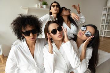 Funny young multiracial girls wear sunglasses bathrobes looking at camera
