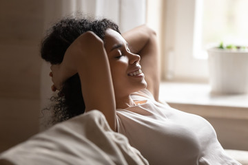 Happy biracial woman relax on couch with eyes closed