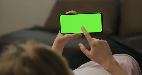 Young woman lying on a couch and using smartphone with horizontal green screen Wall mural