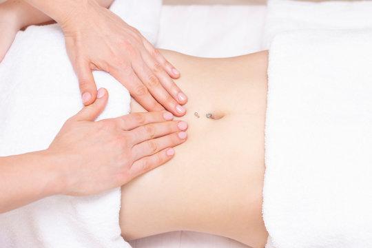 Massage Therapist Massaging a Womens Stomach. Massage and body care. Spa body massage woman hands treatment.