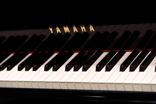 Krakow, Poland - November 21, 2019: YAMAHA piano keyboard and sign in close-up. Yamaha is a Japanese multinational corporation one of the most famous piano producer in the world