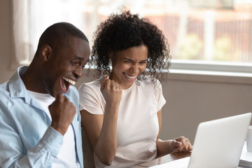Overjoyed multiracial couple triumph with good online news