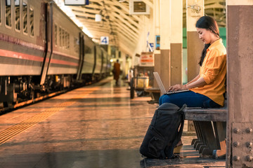 Asian woman using a laptop while waiting for a train at the station
