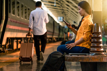 Woman using a phone at the train station. Other people on the plateform