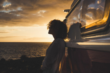 Travel and independence concept with woman in silouette and old vintage camper van - coloured dawn sunset in background with ocean and horizon