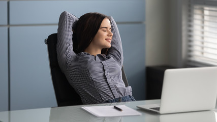Happy female worker relax at workplace with eyes closed