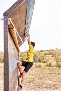 young man climbing a wooden wall in a Spartan race