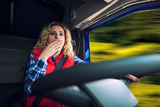 Sleepy and tired truck driver driving truck. Woman female trucker yawning due to tiredness and boredom while steering.