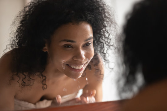 Smiling african American woman wash face in clear water