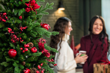 Beautiful happy young two women with smiles on their faces communicate in the kitchen on the background of Christmas decorations and a Christmas tree