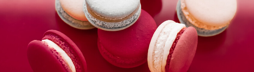 Foto auf Leinwand Macarons French macaroons on wine red background, parisian chic cafe dessert, sweet food and cake macaron for luxury confectionery brand, holiday backdrop design