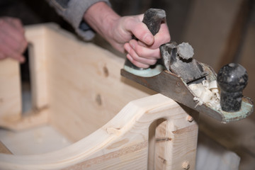 Work with a planer. A man is planing a tree. Building tool. Handle a wooden chair.