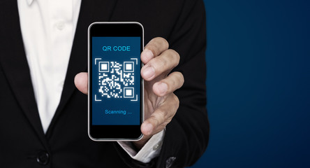 QR code scanning payment and verification. Businessman holding mobile smart phone scan QR code on...