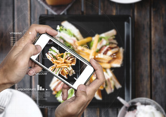 Food Nutrition Scanning Technology, and Healthy eating Lifestyles. a man using mobile smart phone checking nutrition facts of club sandwich and french fries