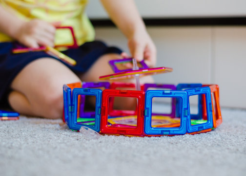 Kid plays with a magnetic constructor toy. A little child girl is playing with colorful blocks. Close up. Girl  playing intellectual toys. Children's magnetic designer for development of motor skills.