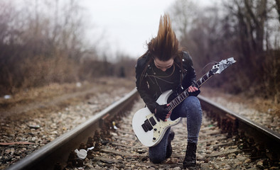 Beautiful young girl rocker with electric guitar. A rock musician girl in a leather jacket with a guitar sings. A rock band soloist plays the guitar and screams into the microphone.