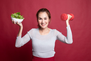 Healthy Asian woman with dumbbells and salad.