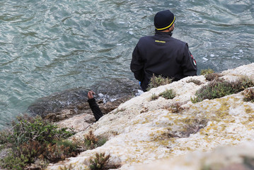 A rescue worker brings bodies to shore after a migrant boat capsized off the Italian coast, on the island of Lampedusa