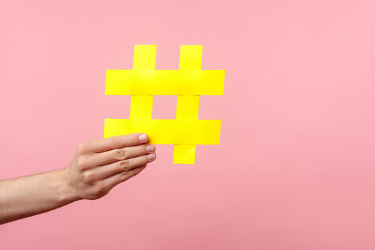 Closeup of male hand holding large yellow hashtag sign, concept of marketing and promotion in internet, followers in social media, trend content. indoor studio shot isolated on pink background