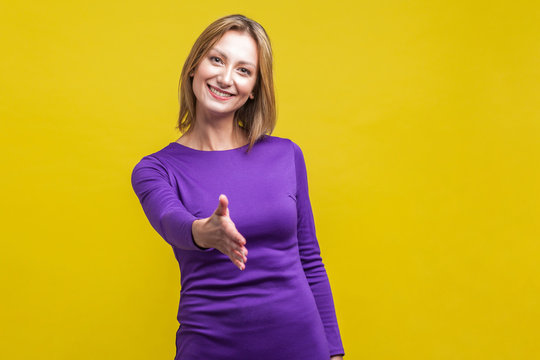 Let me introduce myself. Portrait of friendly woman in elegant tight purple dress giving hand to handshake, greeting guests with toothy smile. indoor studio shot isolated on yellow background