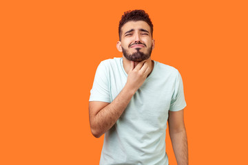 Inflamed throat. Portrait of sick brunette man with beard in white t-shirt touching painful neck,...