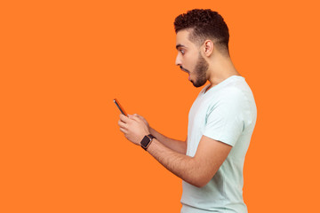 Side view of amazed brunette man with beard in white t-shirt looking shocked at mobile phone, pleasantly surprised by good gadget, application. empty copy space for advertisement, indoor studio shot