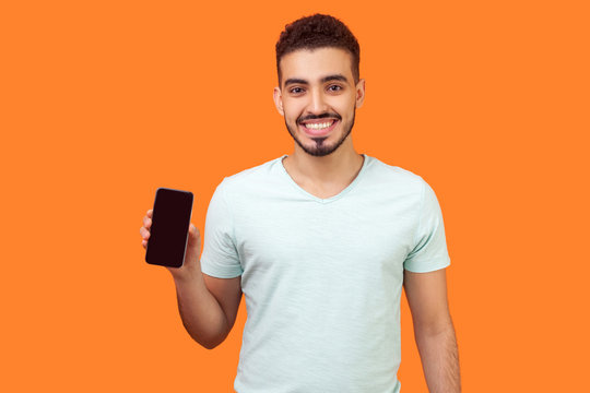 Portrait of positive brunette man with beard in white t-shirt holding cellphone and smiling, looking satisfied with device or mobile data tariffs. indoor studio shot isolated on orange background