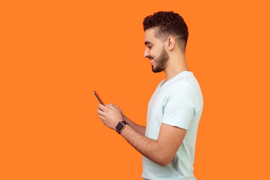 Side view of happy brunette man with beard in white t-shirt smiling while using cellphone, chatting in social media, enjoying mobile service. empty copy space for advertisement, indoor studio shot